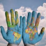 the world map painted onto two human hands